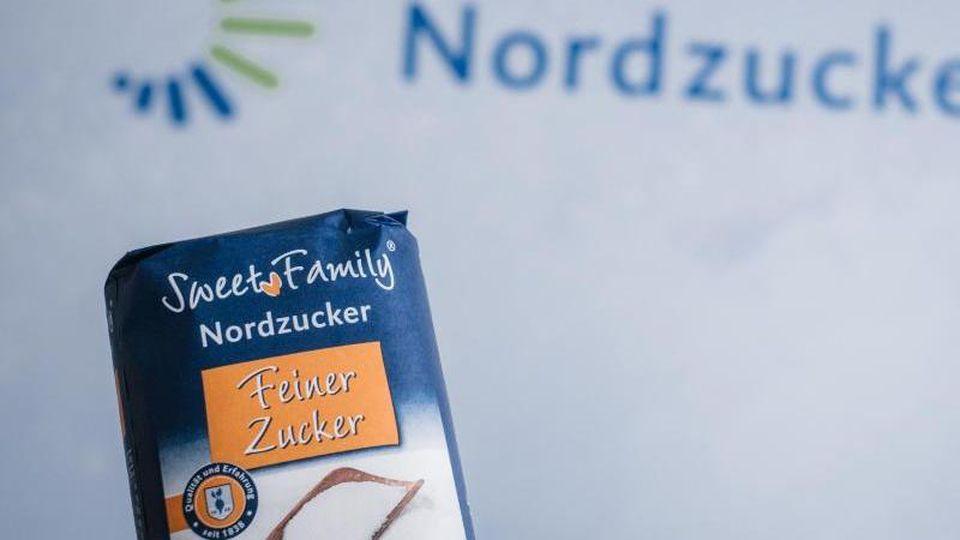 Ein Packet Zucker vor dem Logo der Nordzucker AG. Foto: Ole Spata/dpa/Archivbild