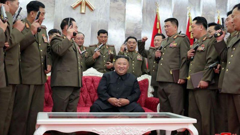 Nordkoreas Machthaber Kim Jong Un (M) sitzt während führende Kommandeure der Armee Waffen in der Hand halten. Foto: KCNA/dpa/Archiv