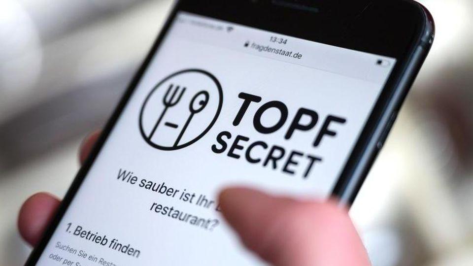"""Eine Frau bedient ein Smartphone, auf dem die Webpräsenz der Plattform """"Topf Secret"""" geöffnet ist. Foto: Marijan Murat/dpa/Archivbild"""