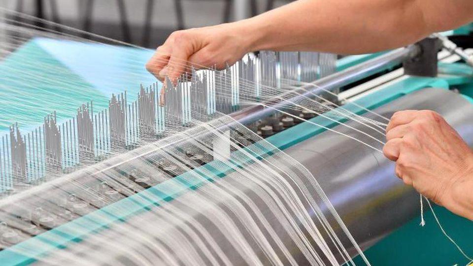 Eine Mitarbeiterin bestückt in einer Textilweberei die sogenannte Zettelmaschine mit Garn. Foto:MartinSchutt/Archiv