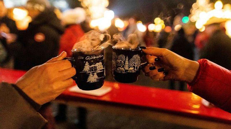 Zwei Besucherinnen stoßen auf einem Weihnachtsmarkt mit Glühwein an. Foto: Philipp von Ditfurth/dpa/Symbolbild