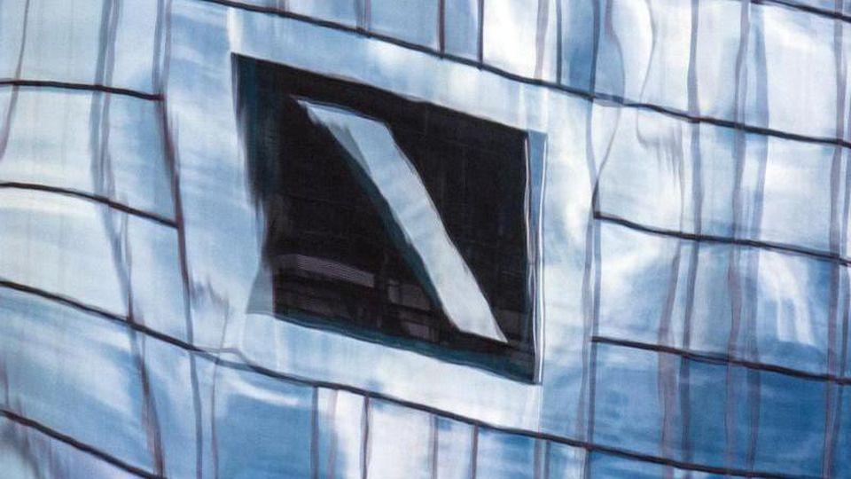 Zentrale der Deutschen Bank in einer Glasfassade gespiegelt. Insgesamt rund 70.000 Privatkunden der Deutschen Bank können derzeit ihre Kredite nicht bedienen. Foto: Boris Roessler/dpa