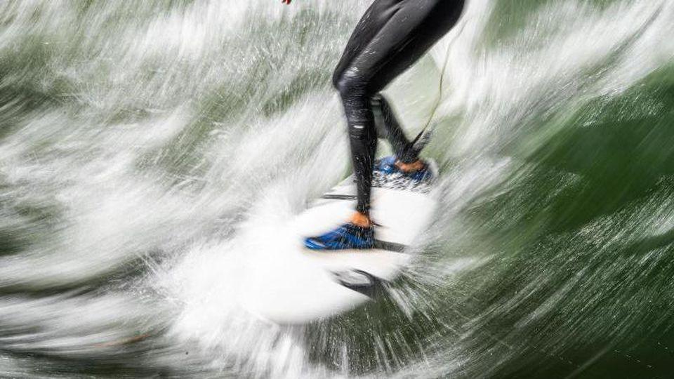 Ein Eisbachsurfer springt mit seinem Surfbrett auf die Eisbachwelle. Foto: Lino Mirgeler/dpa/Archivbild