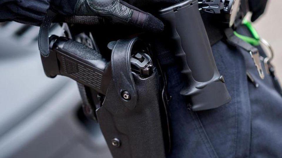 Ein Polizeibeamter trägt die Dienstwaffe am Gürtel. Foto:Hauke-Christian Dittrich/Archivbild