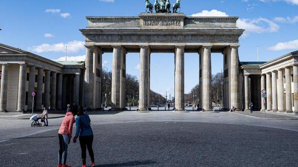 Zwei Joggerinnen machen auf dem sonst gut besuchten Pariser Platz vor dem Brandenburger Tor in Berlin ein Selfie. Foto: Fabian Sommer/dpa