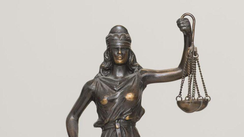 """Eine Figur """"Justitia"""" steht in einem Landgericht auf einem Schreibtisch. Foto: Patrick Seeger/dpa"""