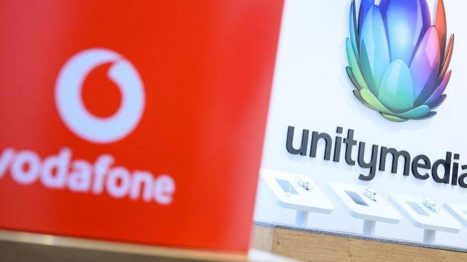 Eine Box mit dem Logo von Vodafone steht in einem Shop des Unternehmens vor einem Logo von Unitymedia. Foto: Sebastian Gollnow/dpa