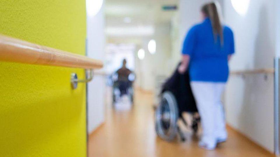 Eine Pflegerin schiebt eine Bewohnerin eines Pflegeheims in einem Rollstuhl über den Flur. Foto: Tom Weller/dpa/Archivbild