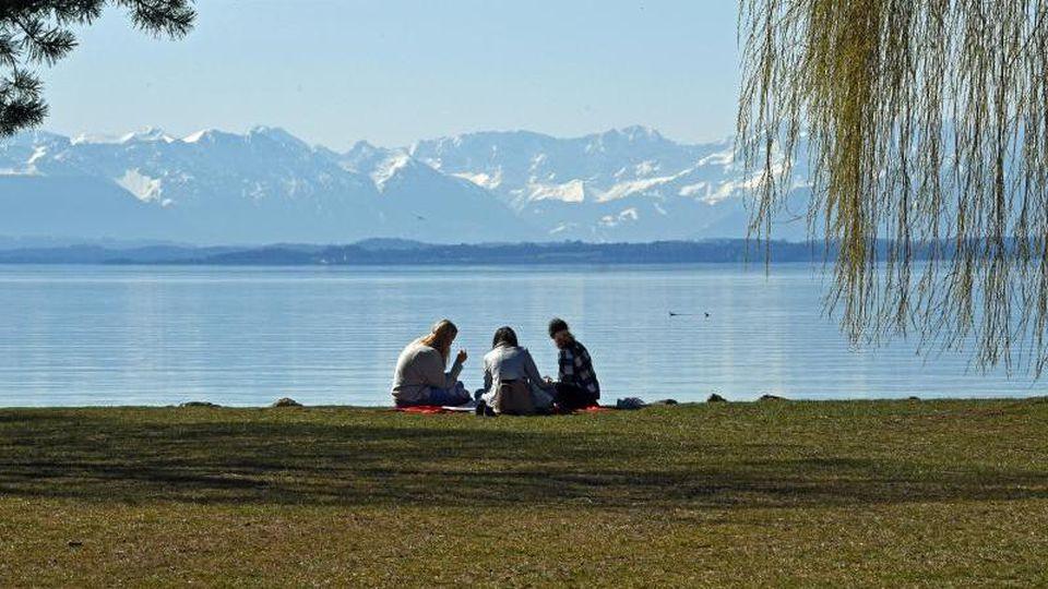 Drei Mädchen sitzen am See. Foto: Ursula Düren/dpa/Symbolbild