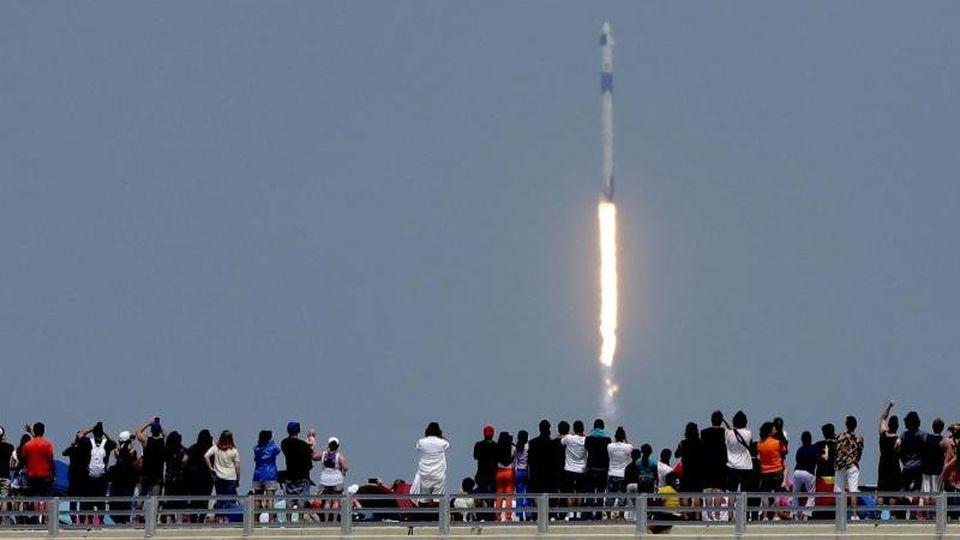"""Zuschauer beobachten den Start der """"Falcon 9""""-Rakete vom Weltraumbahnhof Cape Canaveral. Foto: Charlie Riedel/AP/dpa"""
