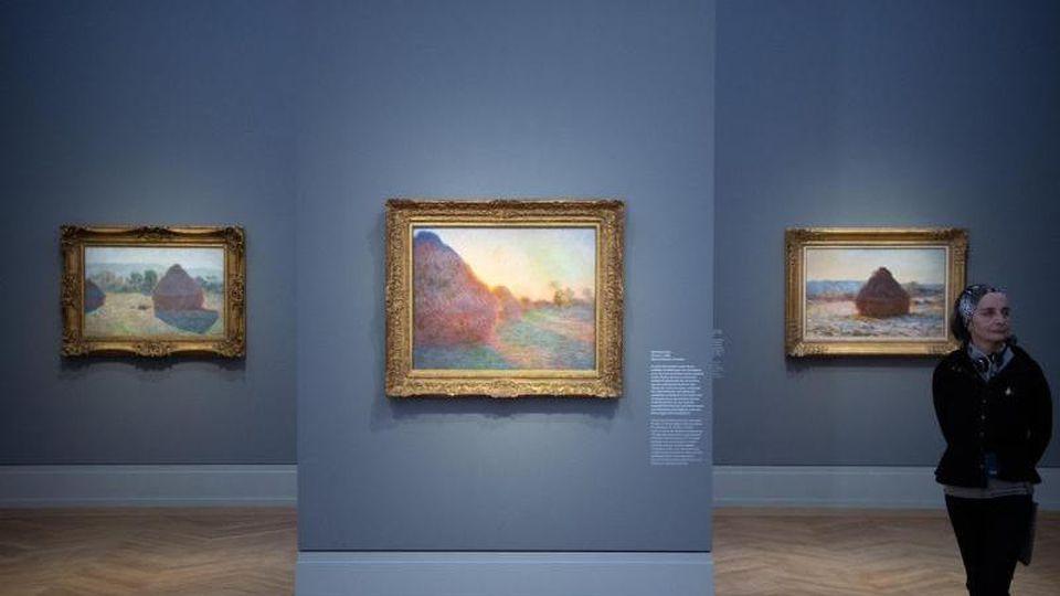 """Eine Fau geht während des Presserundgangs zur Ausstellung """"Monet.Orte"""" im Museum Barberini an den Bildern """"Getreideschober in der Mittagssonne"""" (1890), """"Getreideschober"""" (1890) und """"Verschneiter Getreideschober in der Sonne"""" (1891, r) vorbei. Die Ausstell"""