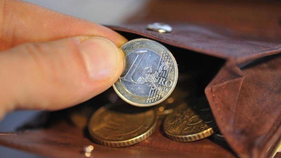 Eine Hand nimmt eine Euro-Münze aus einer Geldbörse, in der sich weitere Münzen befinden. Foto: Andreas Gebert/Archiv
