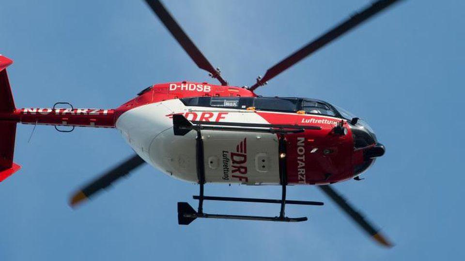 Ein Rettungshunschrauber fliegt über einem Klinikum. Foto: Stefan Sauer/zb/dpa/Symbolbild
