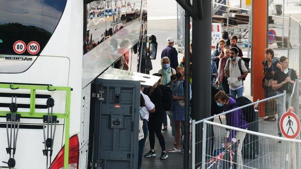 Reisende bringen ihr Gepäck auf dem Zentralen Omnibusbahnhof (ZOB) in den Reisebus. Foto: Annette Riedl/dpa/Archivbild
