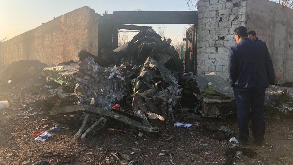 Iran Teheran Männer stehen neben Trümmern nach einem Flugzeugabsturz am Rande von Teheran. Bei dem Absturz der ukrainischen Passagiermaschine nahe Teheran sind nach Angaben der Hilfsorganisation iranischer Halbmond alle Insassen ums Leb