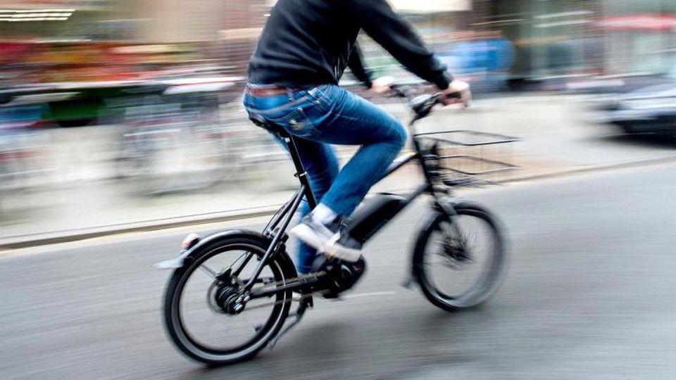 Ein Radfahrer fährt mit einem E-Bike auf einer Straße. Foto: Hauke-Christian Dittrich/dpa/Symbolbild