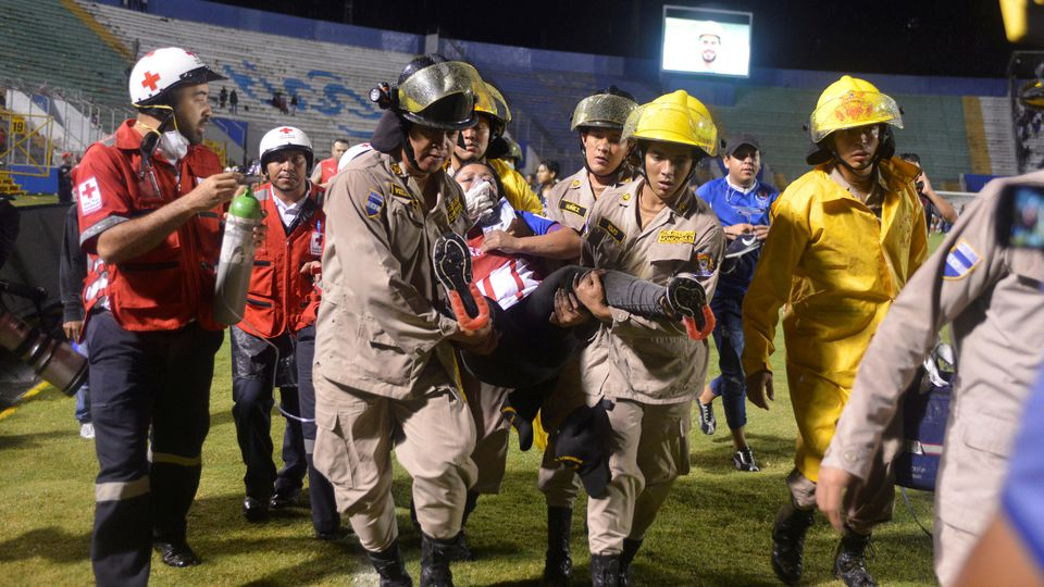 Firefighters carry a woman after three people died in riots before a soccer match when the fans attacked a bus carrying one of the teams, at the National Stadium in Tegucigalpa