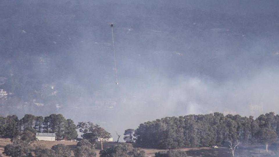 Ein Löschhubschrauber ist bei einem Buschfeuer in der Nähe der australischen Hauptstadt Canberra im Einsatz. Foto: Liu Changchang/XinHua/dpa