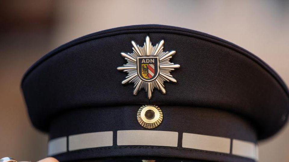 EIn Polizist mit Polizeimütze. Foto: Daniel Karmann/dpa/Archivbild