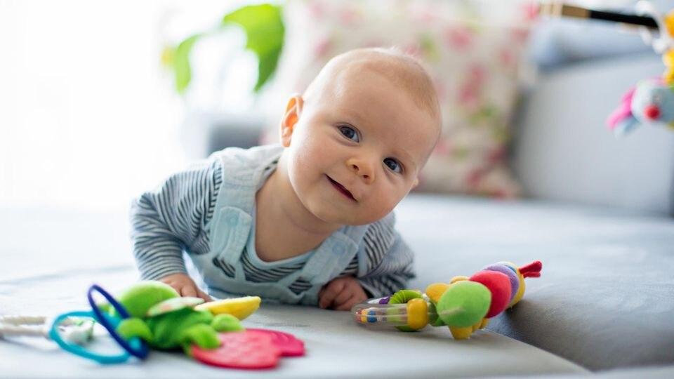 Mit Spielzeug können Eltern das Baby dazu bewegen, sich herumzurollen und damit einen ersten Schritt zur eigenen Mobilität zu tun.
