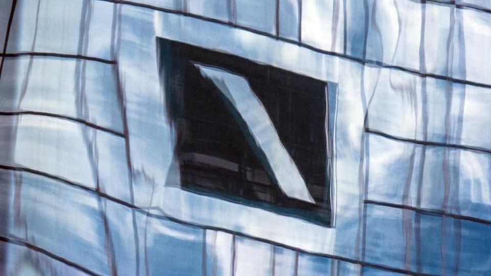 Die Zentrale der Deutschen Bank spiegelt sich in einer Glasfassade. Foto: Boris Roessler/dpa/Archivbild