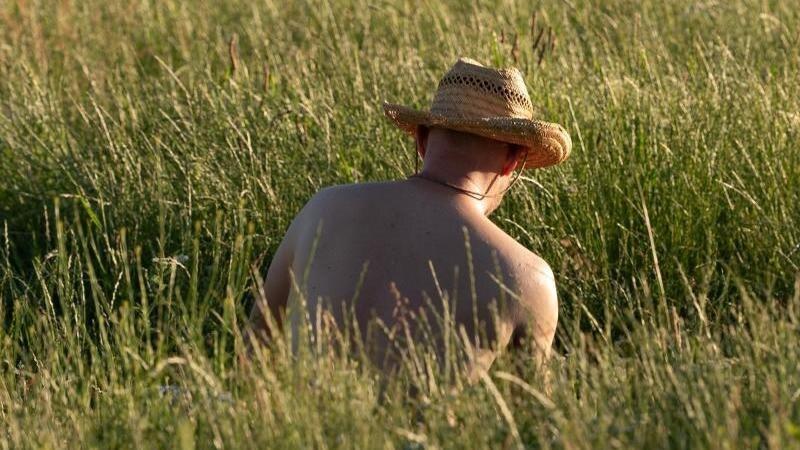 Ein Mann mit Strohhut sitzt auf einer Wiese. Foto: Sebastian Kahnert/dpa-Zentralbild/dpa/Archivbild