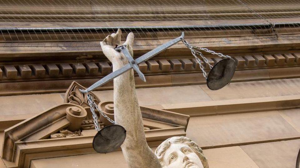 Vor einem Gericht hält eine Statue der Justitia eine Waage in der Hand. Foto: Stefan Puchner/dpa/Archivbild