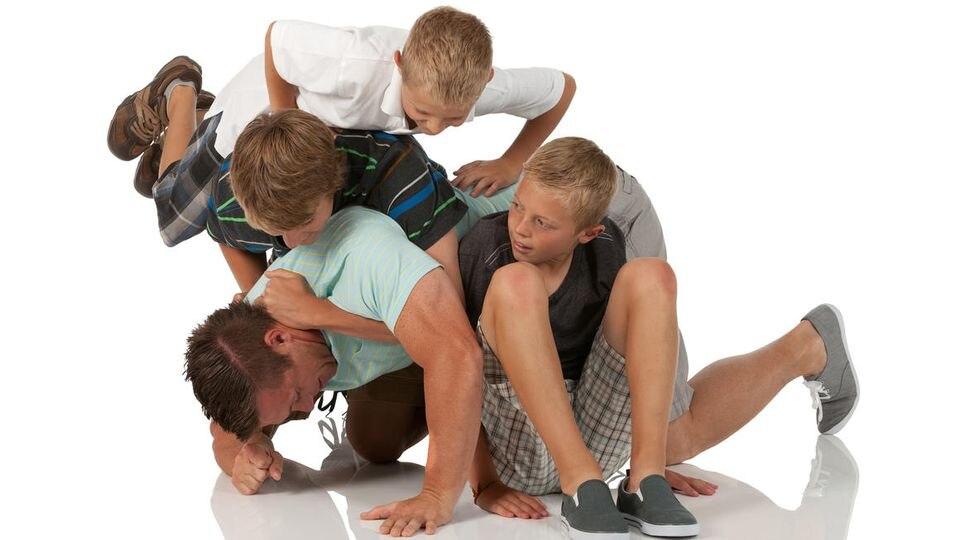 Kinder toben mit einem Erwachsenen (Symbolbild)