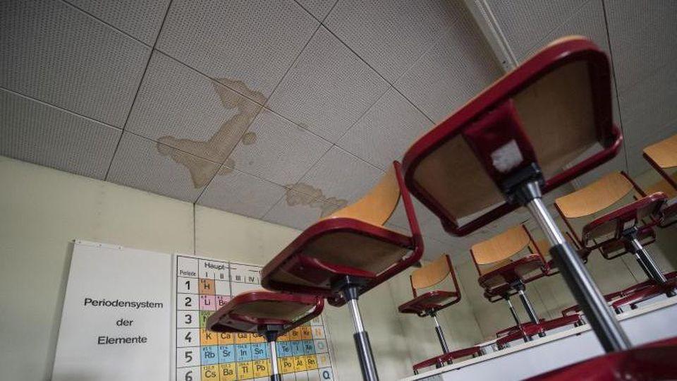Schäden sind an der Decke eines Unterrichtsraums zu sehen. Foto: Marijan Murat/dpa/Archivbild