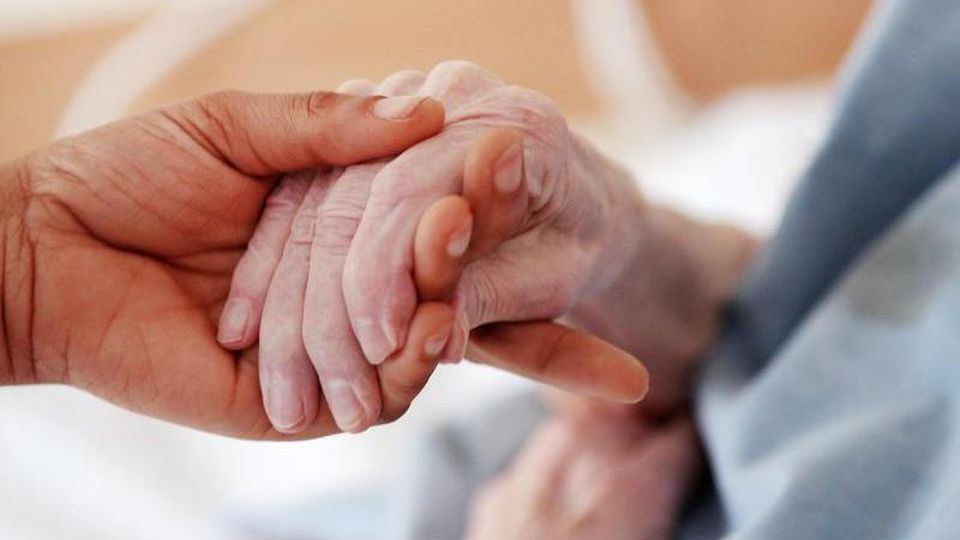 Eine Pflegerin hält in einem Altenheim die Hand einer Bewohnerin. Foto: Oliver Berg/dpa/Archivbild