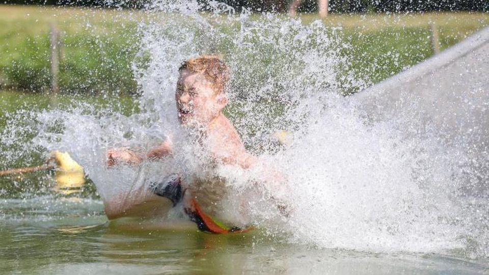 So lässt es sich die Hitze aushalten:Ein Junge rutscht eine Wasserrutsche hinunter. Foto: Thomas Warnack/dpa