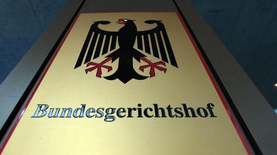 """Ein Hinweisschild mit Bundesadler und Schriftzug """"Bundesgerichtshof"""". Foto:Uli Deck/Archivbild"""