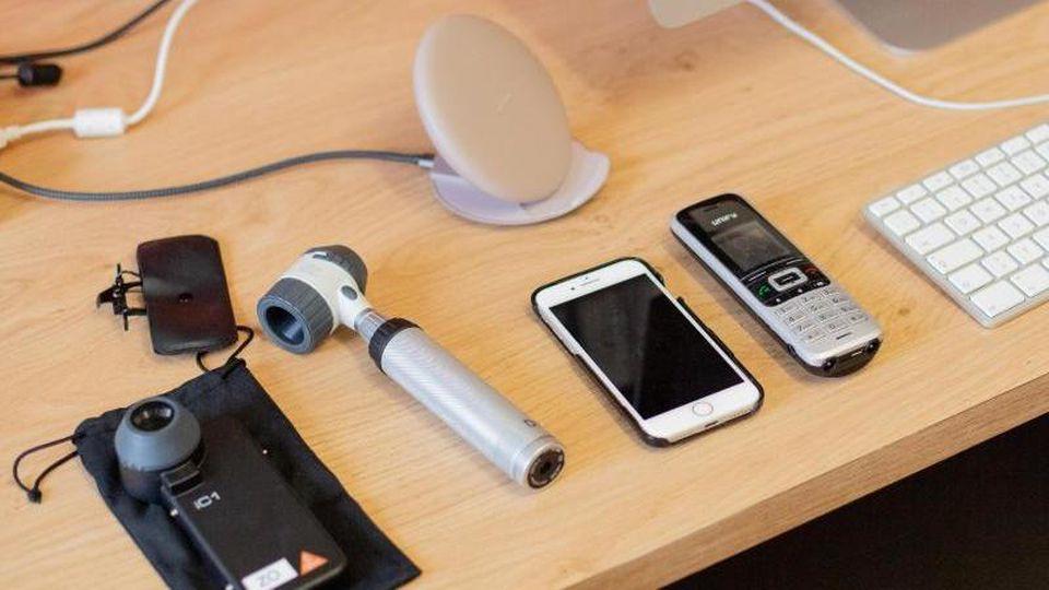 Ein Computer, ein Handy, ein Telefon sowie Untersuchungsgeräte für Dermatologie liegen in der Praxis einer Fachärztin. Foto: Christoph Soeder/dpa-Zentralbild/dpa