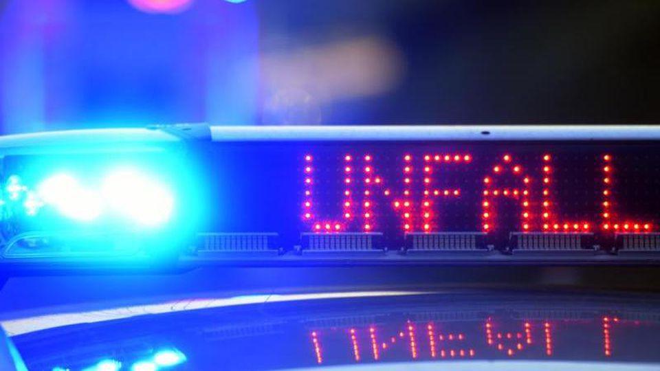 Auf einem Polizeifahrzeug warnt eine Leuchtschrift vor einer Unfallstelle. Foto: Stefan Puchner/dpa/Archiv