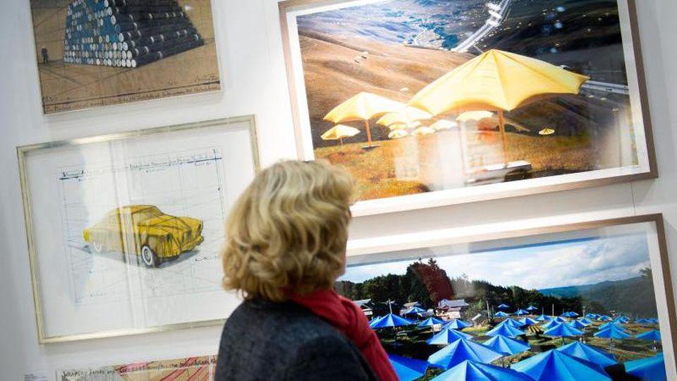 """Eine Frau betrachtet Bilder auf der Kunstmesse """"Affordable Art Fair"""" in Hamburg. Foto: Daniel Reinhardt/dpa/Archivbild"""