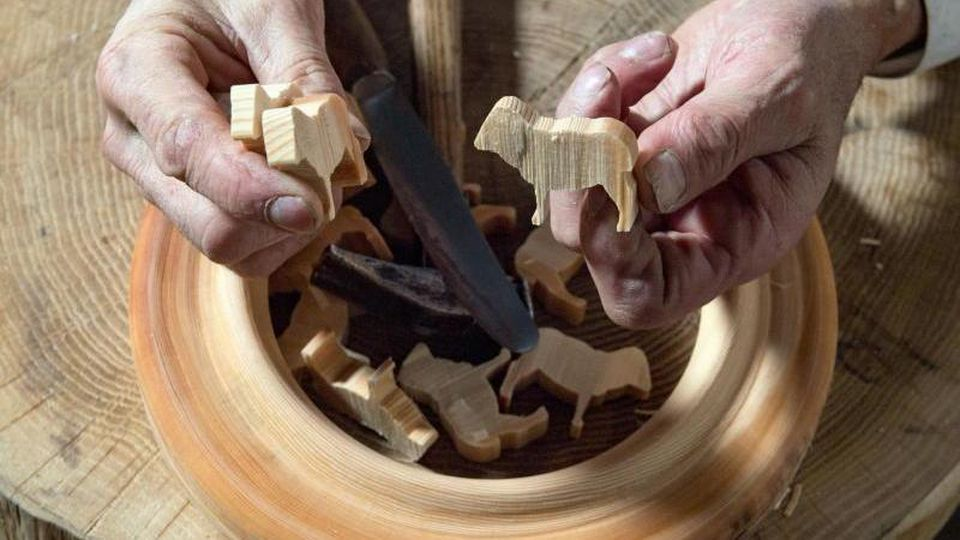 Holzspielzeugmacher und Reifendreher Christian Werner spaltet in seiner Werkstatt in Seiffen Reifentiere aus einem Fichtenreifen. Foto: Hendrik Schmidt/dpa-Zentralbild/dpa
