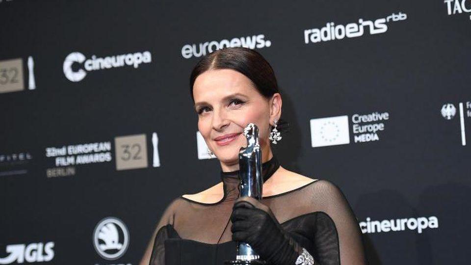 Juliette Binoche mit ihrem Preis (European Achievement in World Cinema) bei der Verleihung in Berlin. Foto: Britta Pedersen/dpa-Zentralbild/dpa
