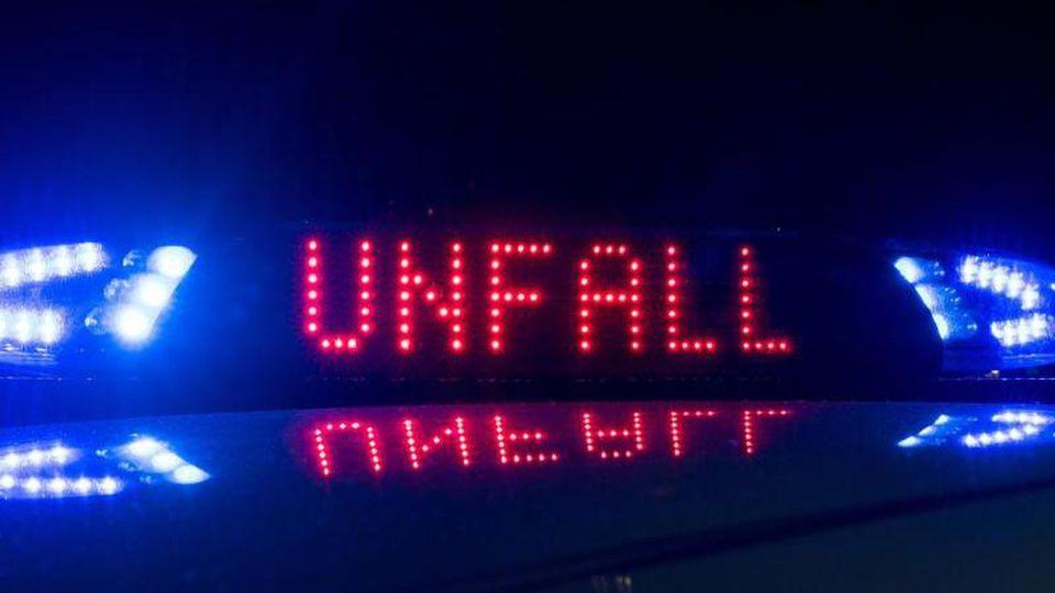 """Blaulicht leuchtet auf dem Dach eines Polizeiwagens, auf dem Display ist der Hinweis """"Unfall"""" zu lesen. Foto: Monika Skolimowska/Archiv"""