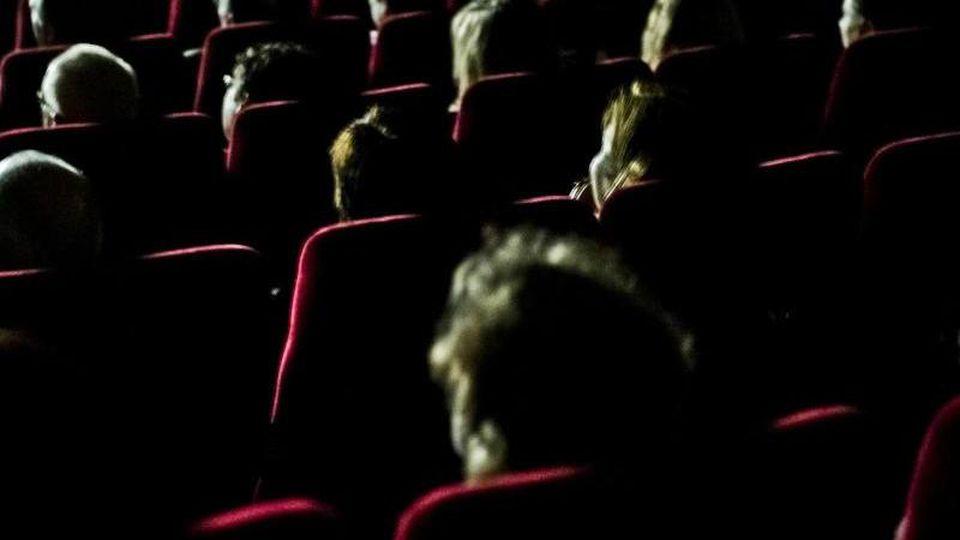 Besucher sitzen in einem Kino. Foto: Nicolas Armer/dpa/Archivbild