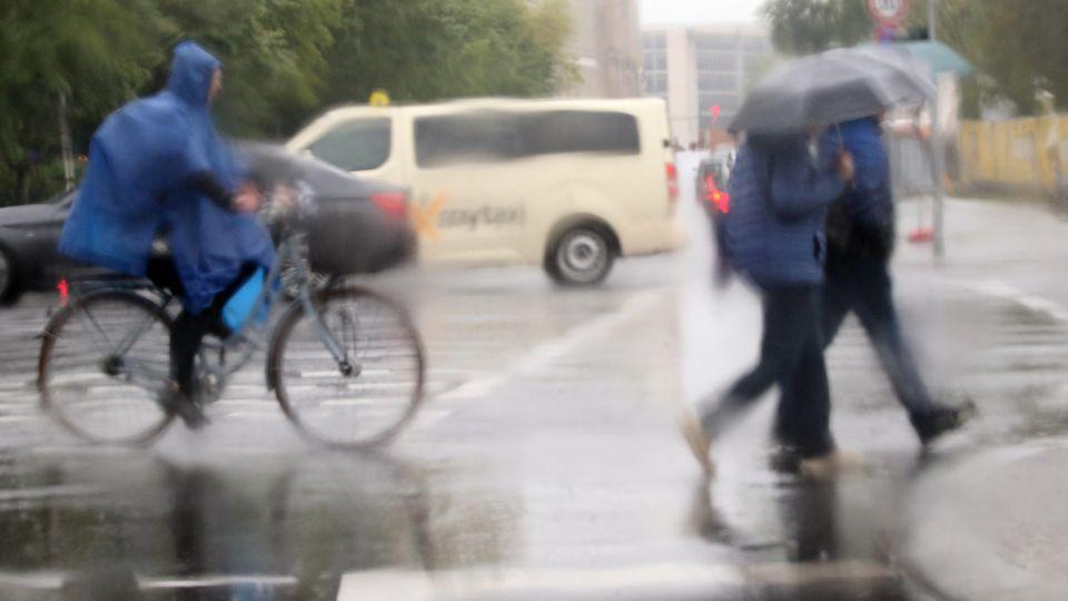 16.05.2019, Berlin: Bei Temperaturen um acht Grad Celsius und Regen bewegen sich Passanten und Radfahrer mit Regenschirmen und Regencape durch den Verkehr. Fotografiert durch das Fenster eines Autos.