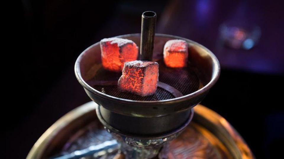 Glühende Kohle liegt auf einem Metallsieb über dem Tabak im Kopf einer Wasserpfeife. Foto: Christian Charisius/Archiv