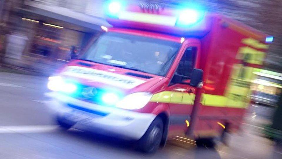 Ein Rettungswagen der Feuerwehr mit Blaulicht fährt eine Straße entlang. Foto: Darmstadt/Archivbild