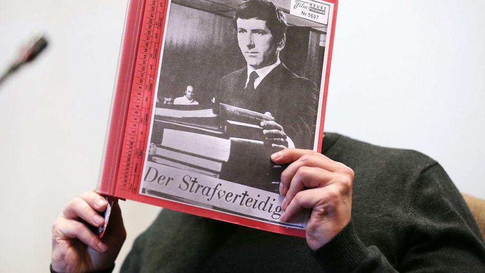 """Jörg L. sitzt zu Beginn eines Prozesstages wegen schweren sexuellen Missbrauchs von Kindern im Gerichtssaal, während er sich eine Mappe mit aufgeklebten Fotos von Filmszenen des Films """"Der Strafverteidiger"""" vor das Gesicht hält"""