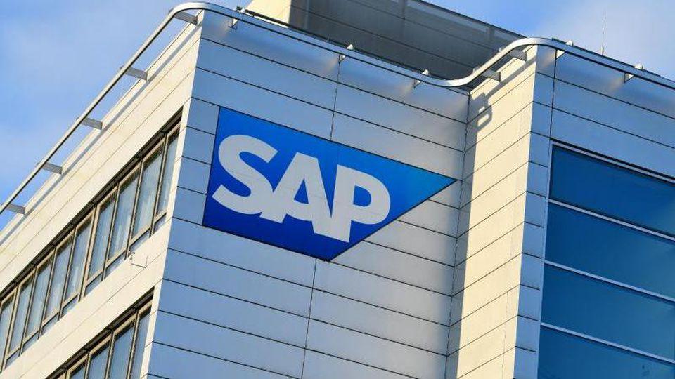 Ein Konzernlogo des Softwarekonzerns SAP ist an einem Gebäude der Unternehmenszentrale angebracht. Foto: Uwe Anspach/dpa/Archiv