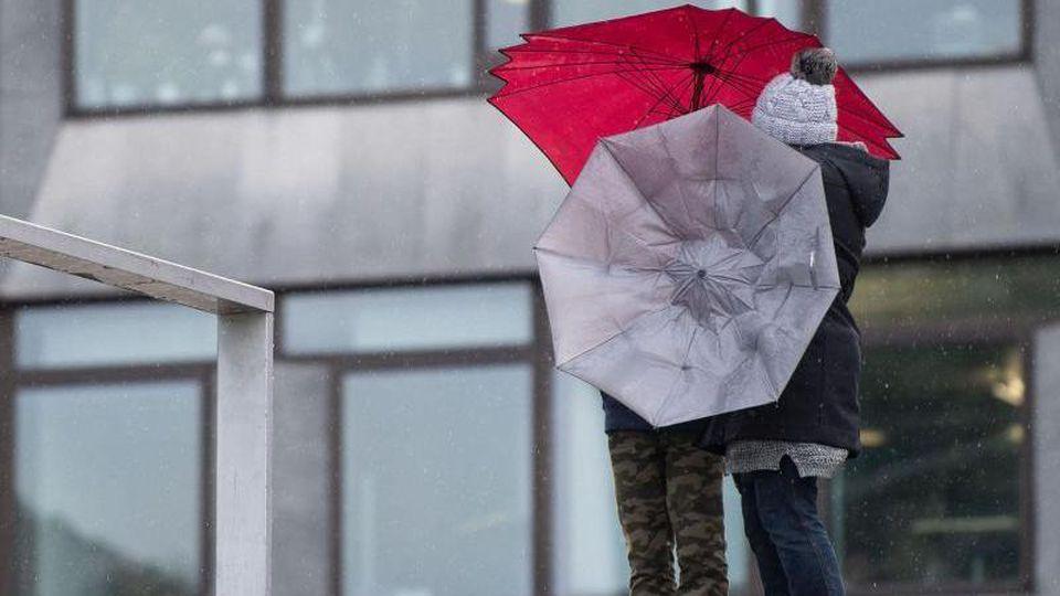 Zwei Passanten hantieren mit ihren Regenschirmen im Wind. Foto: Marijan Murat/Archivbild