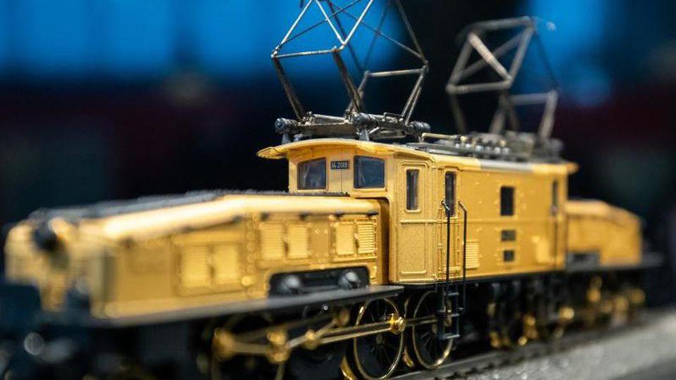 Eine vergoldete Güterzug-Elektrolokomotive von Märklin auf dem Stand des Unternehmens bei der Nürnberger Spielwarenmesse. Foto: Daniel Karmann/dpa