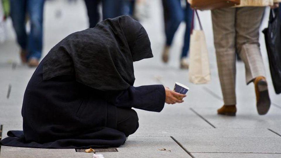 Eine Frau bittet auf der Einkaufsmeile Zeil um Almosen. Foto: Nicolas Armer/dpa/Archivbild
