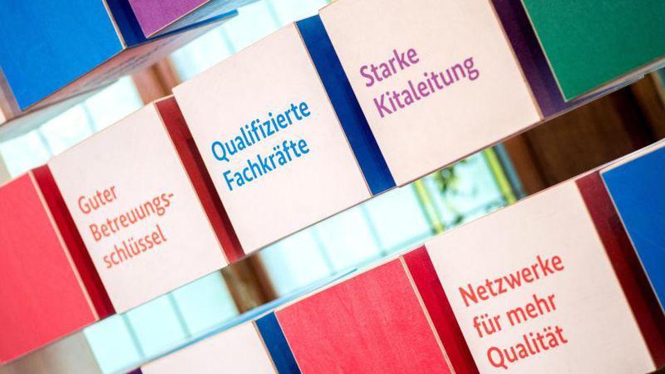 """Bunte Würfel mit verschiedenen Aufschriften zum """"Gute-Kita-Gesetz"""". Foto: Hauke-Christian Dittrich/dpa"""