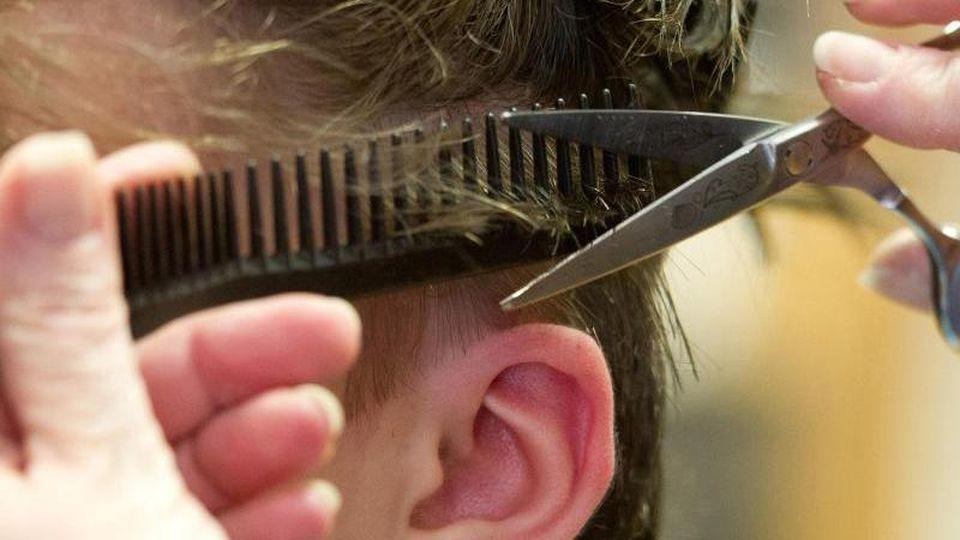 Eine Friseurin schneidet die Haare einer Kundin. Foto: Sebastian Kahnert/dpa/Archivbild