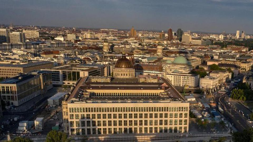 Das Humboldt Forum wird von der aufgehenden Sonne angeleuchtet. Foto: Paul Zinken/dpa/Archivbild